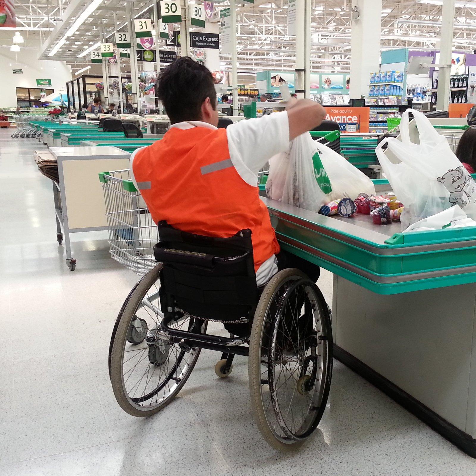 trabajador en silla de ruedas en supermercado
