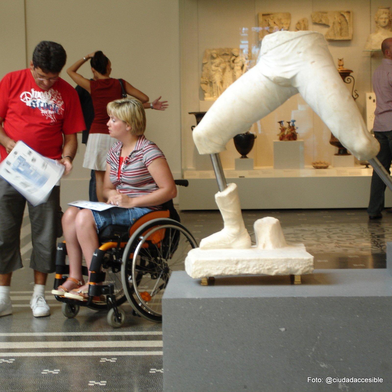 en un museo persona en silla de ruedas observa un catalogo