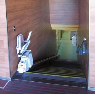 Foto del sillín salva escalera para acceder al nivel -1 del centro deportivo Rolf Nathan