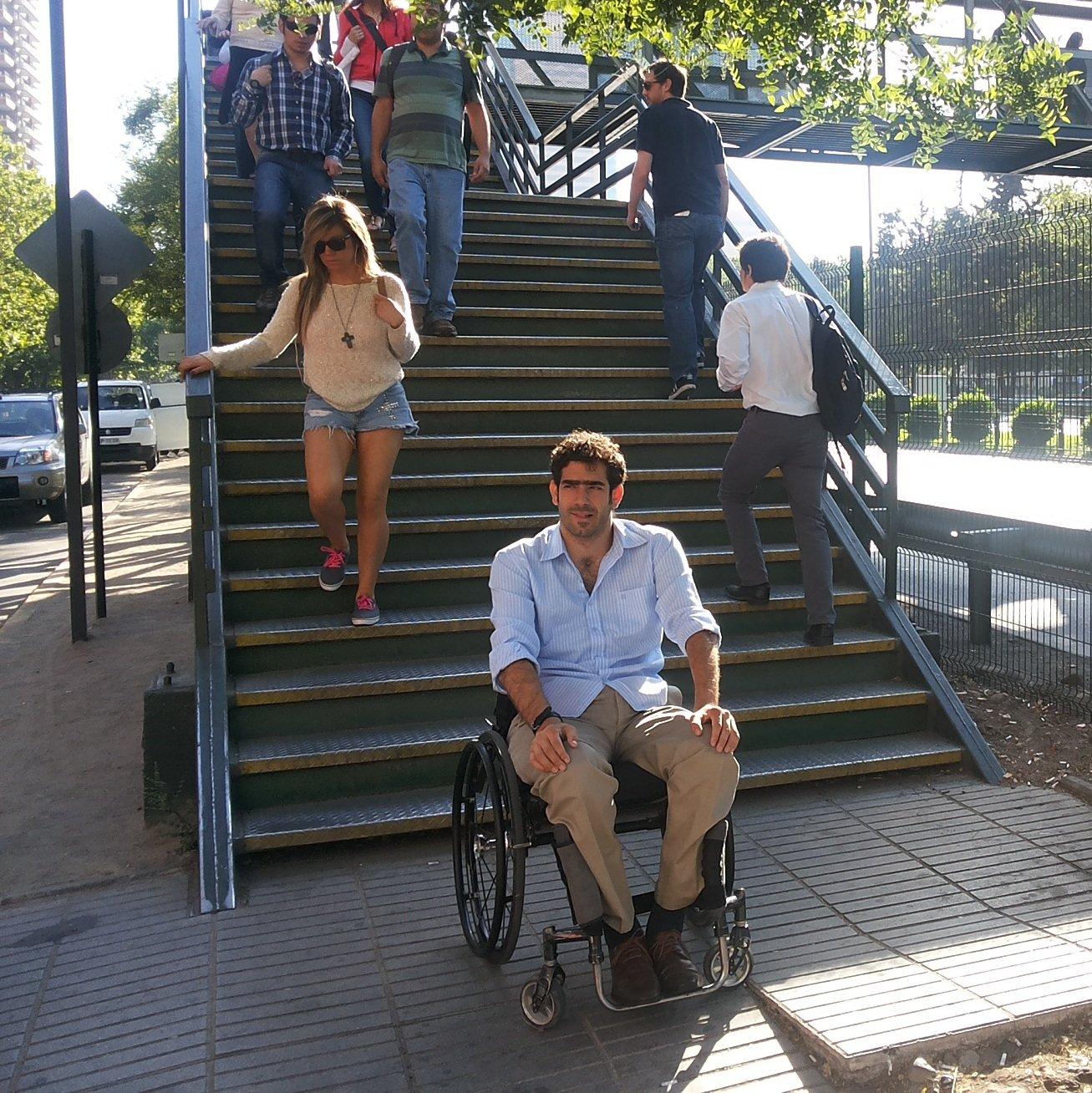 persona en silla de ruedas frente a escaleras de pasarela peatonal