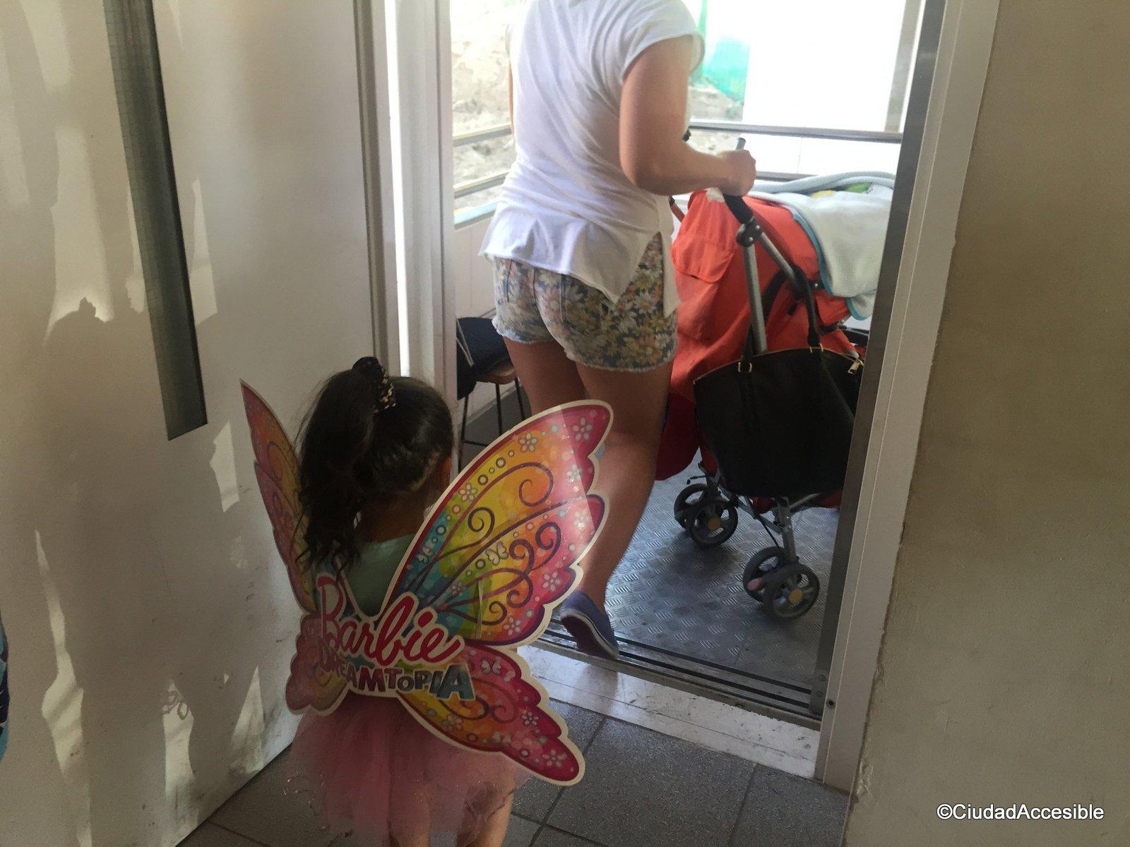 Foto de personas y un coche de niños accediendo al ascensor