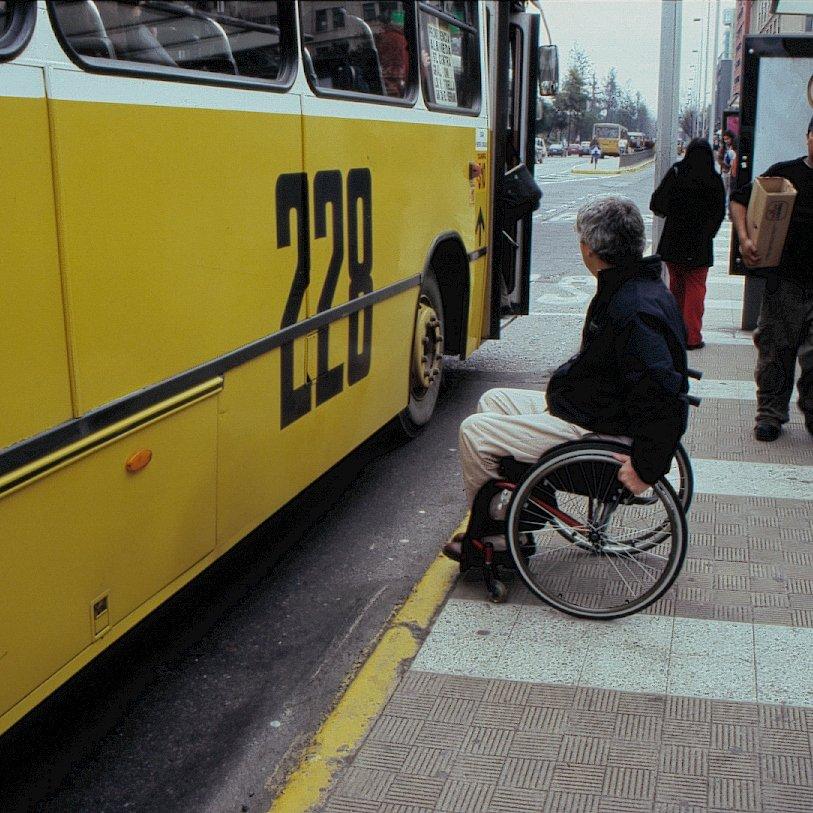 persona en silla de ruedas esperando transporte público