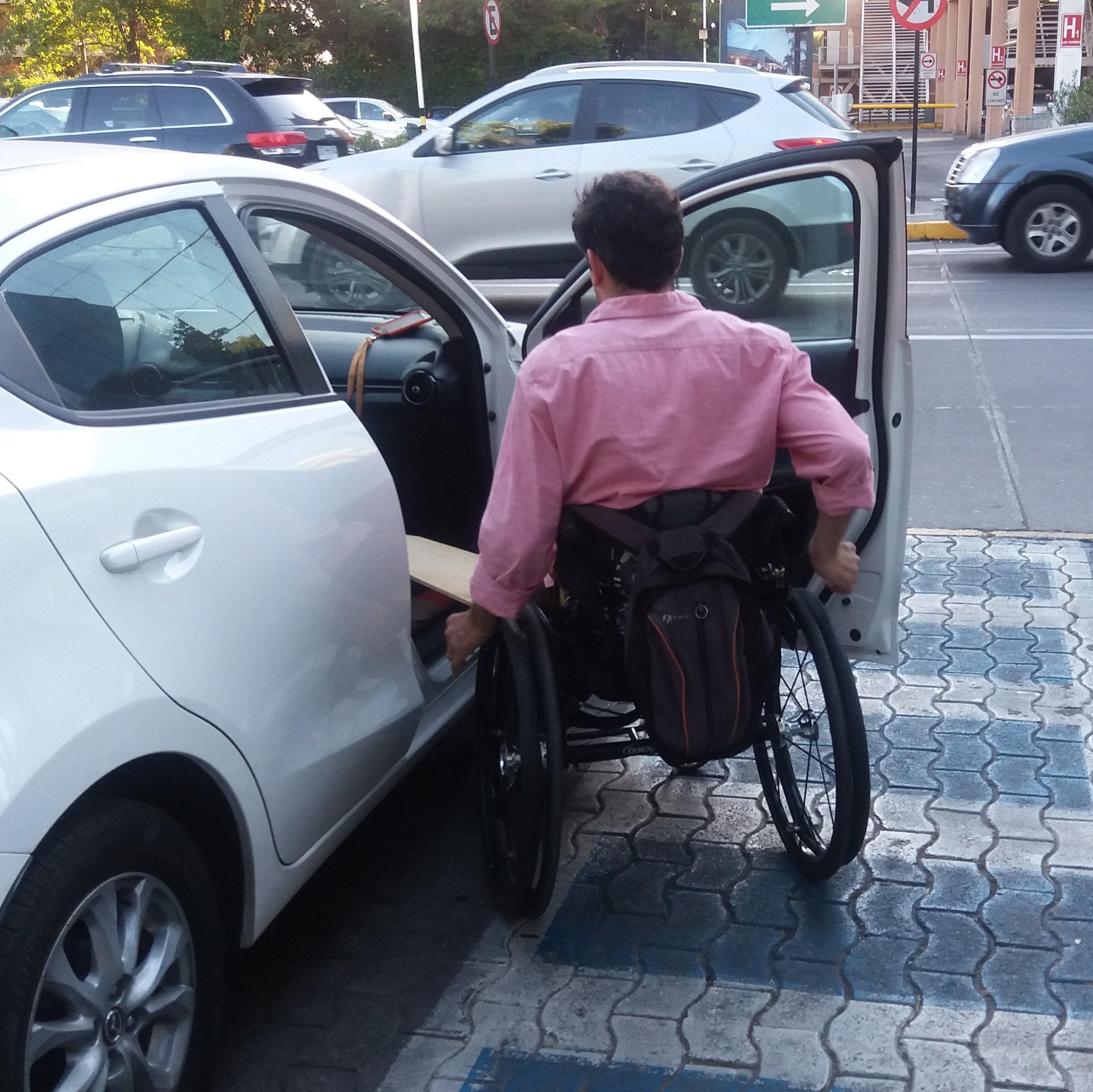 persona en silla de ruedas subiendo a un auto