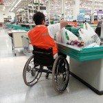 persona en silla de ruedas trabajando como empaquetador de supermercado