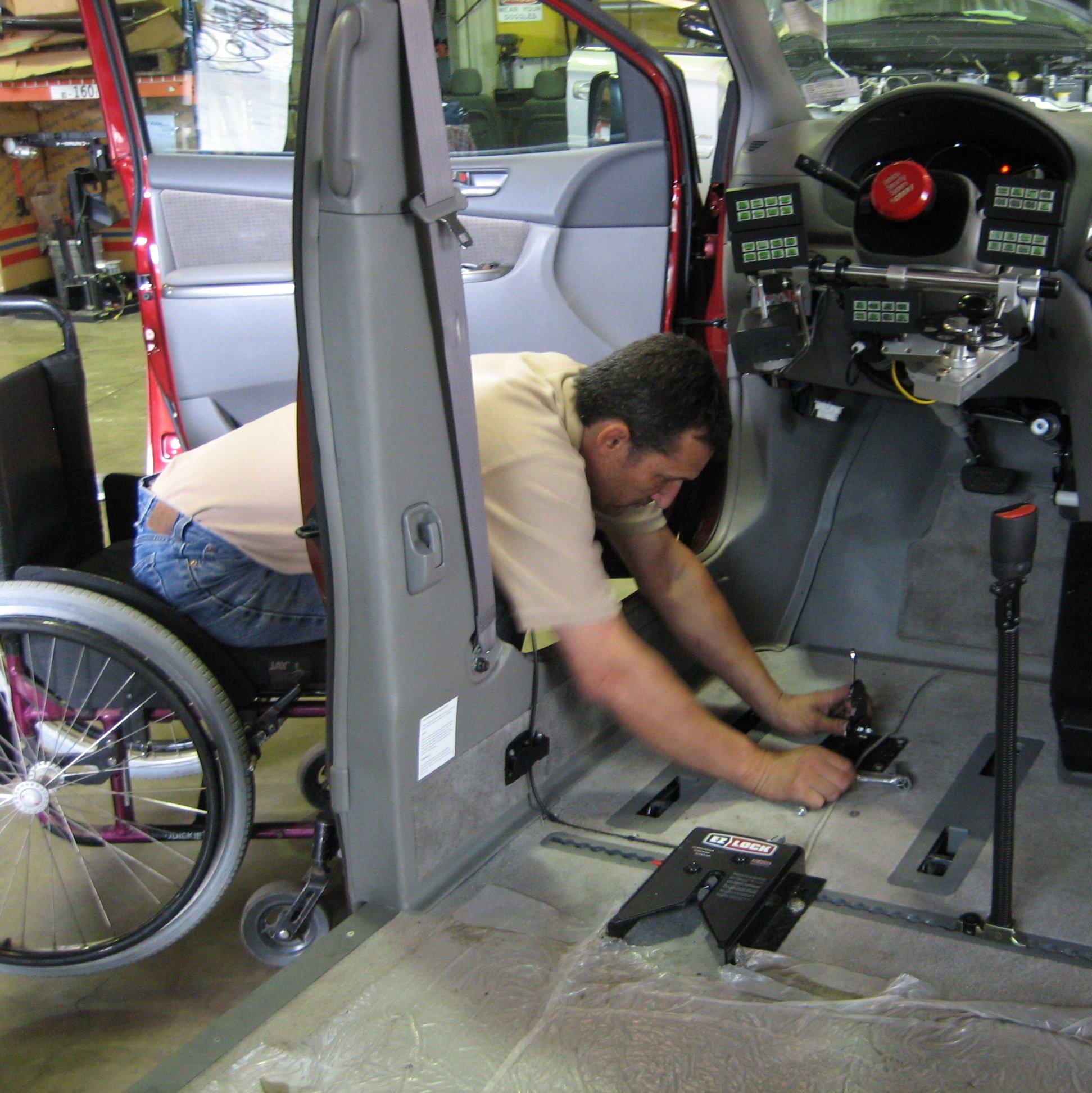 persona en silla de ruedas trabajando en un taller de automoviles