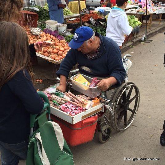 persona en silla de ruedas vendiendo mercadería en una feria