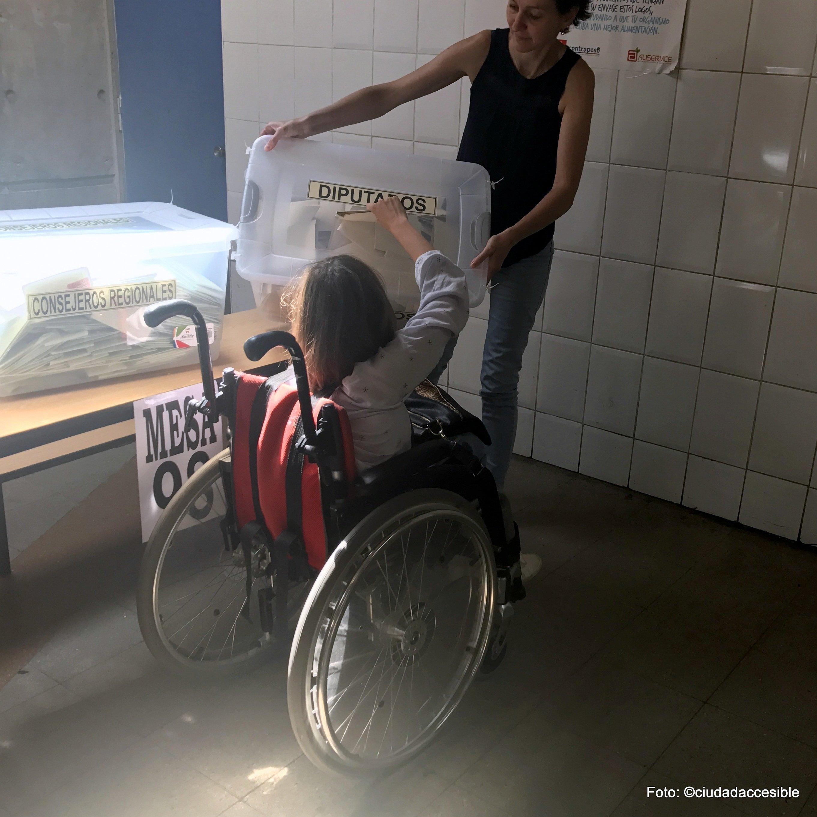 Joven en silla de ruedas deposita su voto