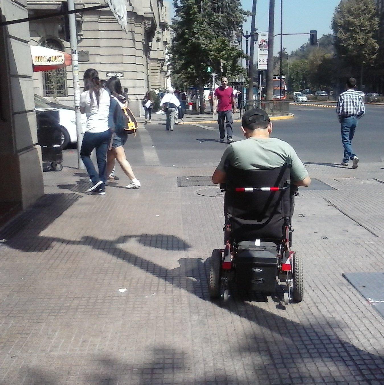 peatón en silla de ruedas circulando por una vereda y enfrentando un cruce