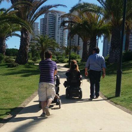 grupo de personas caminando por espacio publico una de ellas en silla de ruedas y otra llevando un coche de niños
