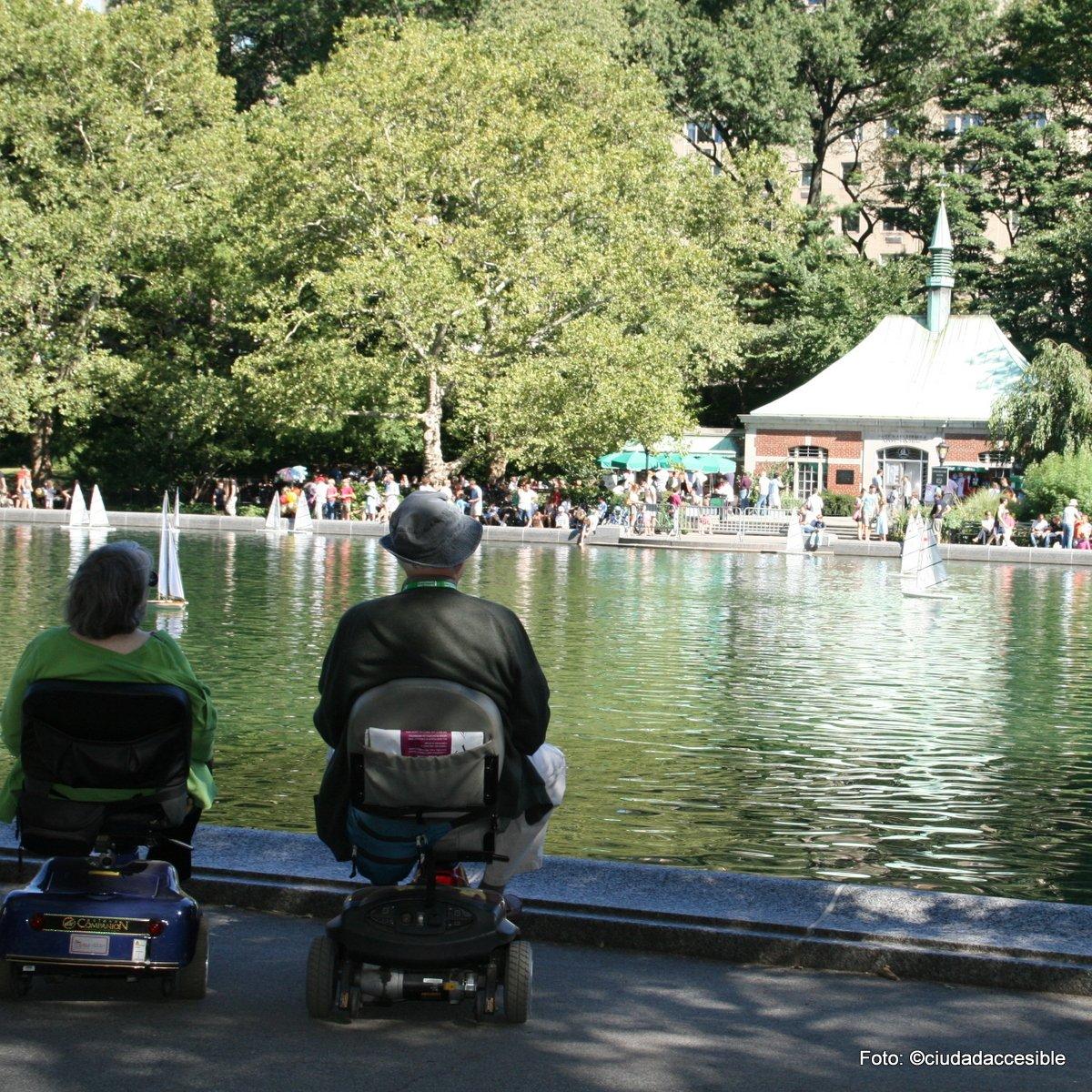 dos adultos mayores en sillas scooter mirando una laguna en parque