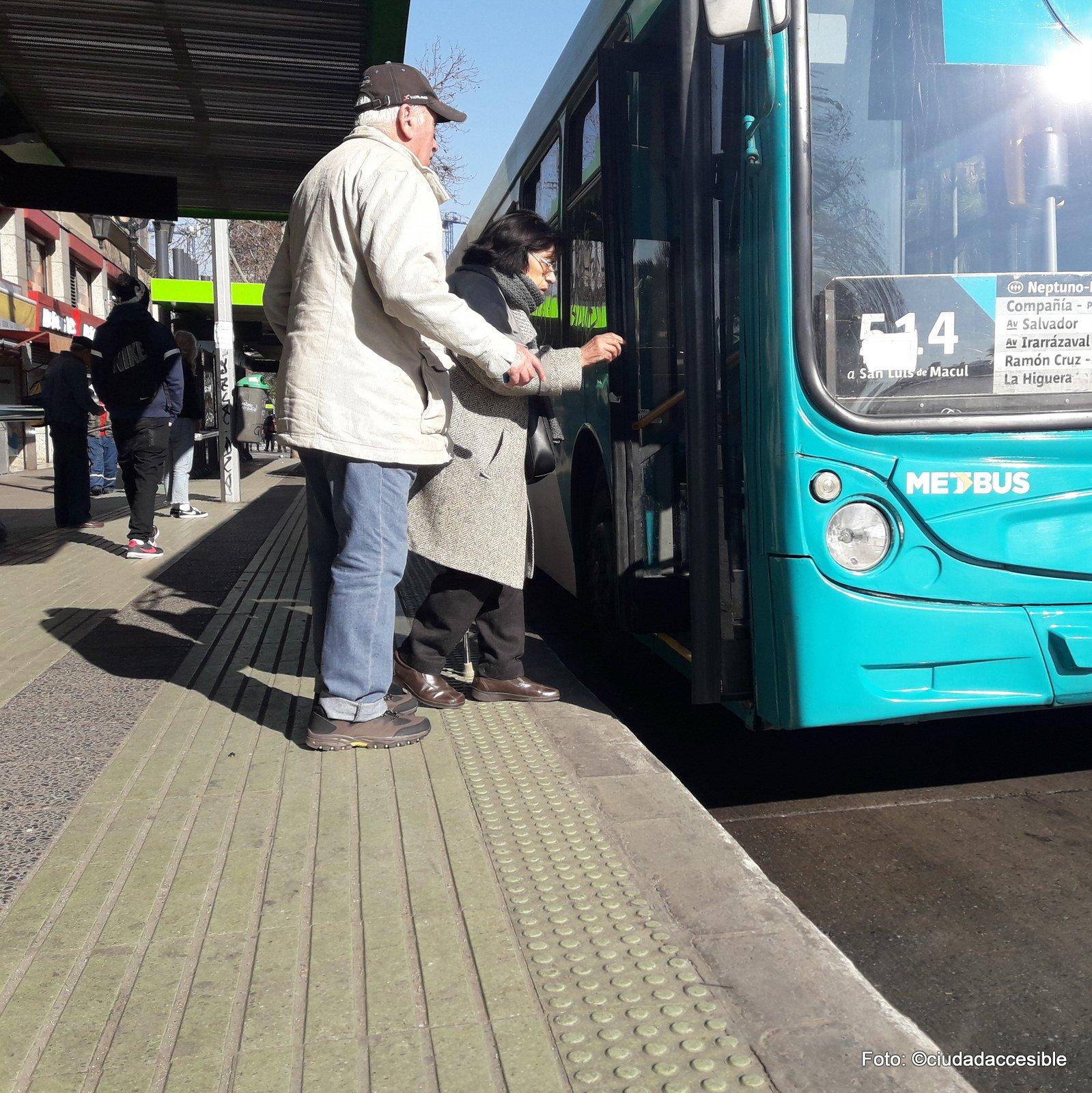 pareja de adultos mayores haciendo ingreso a bus de transporte público