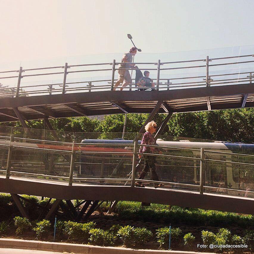 padre con coche y señora mayor suben por la pasarela