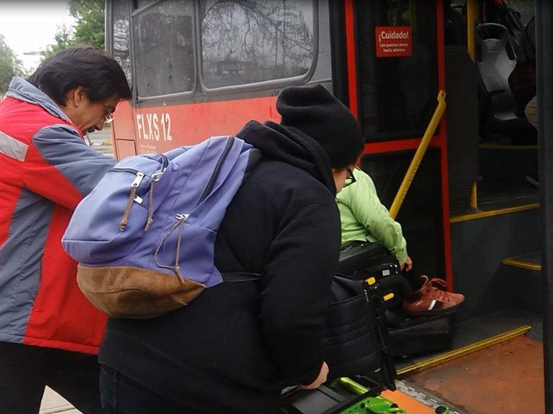dos personas ayudan a otra en silla de ruedas para acceder al bus