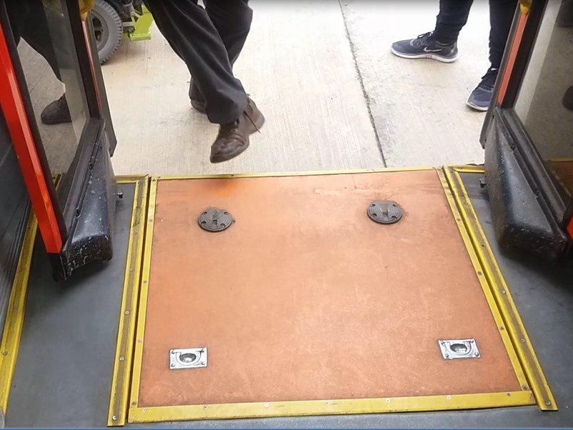 rampa cerrada en el interior del bus que muestra las manillas de difícil manipulación