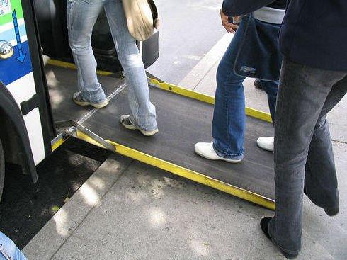 varias personas accediendo al bus por medio de la rampa desplegada en la parte delantera del bus