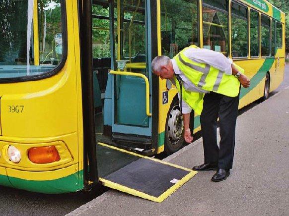 persona desplegando rampa de un bus con un mecanismo de fácil agarre