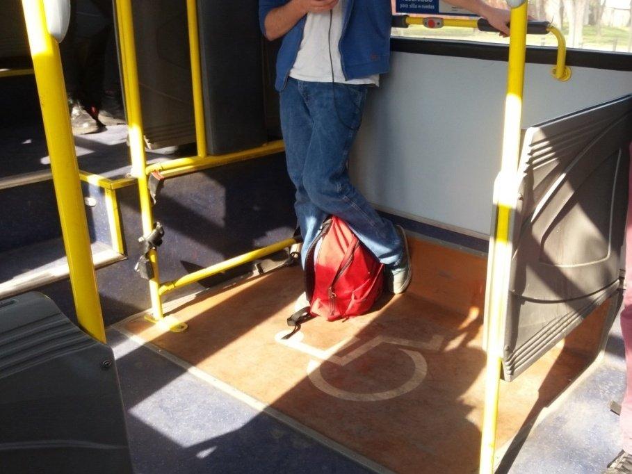 foto de espacio para silla de ruedas en bus con pasamanos de apoyo a una altura muy elevada