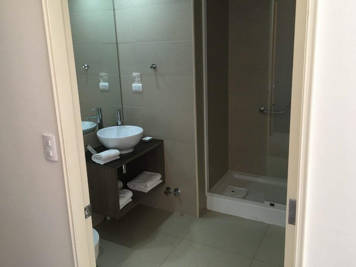 Baño en habitación accesible de hotel con ducha y receptáculo de 10cm y lavamanos con mueble en su parte inferior
