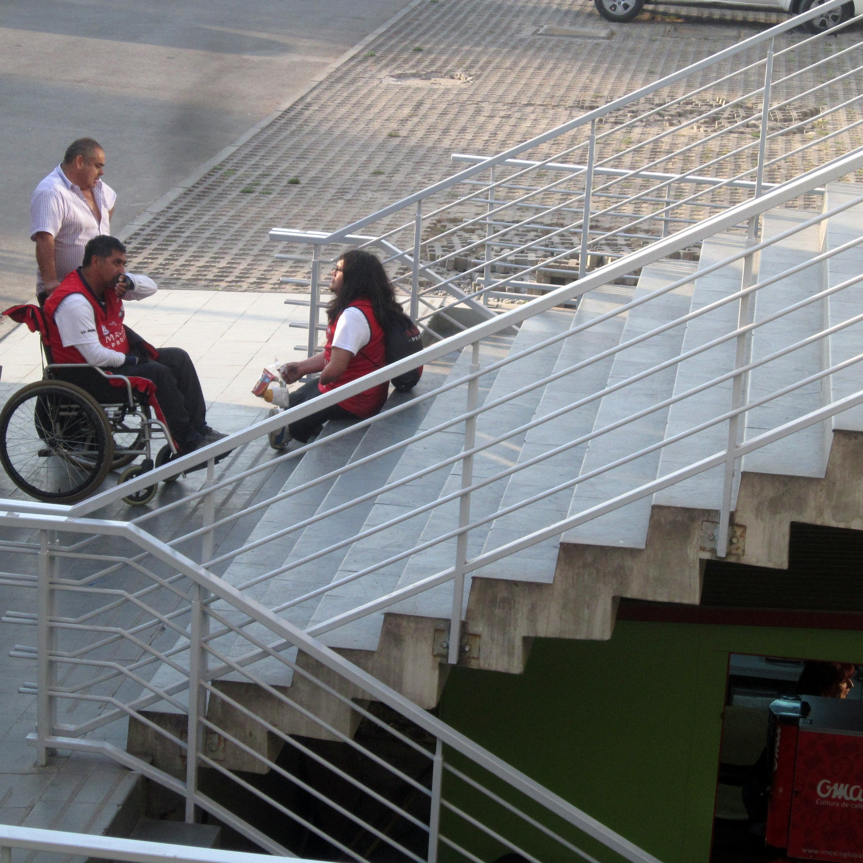 tres personas una en silla de ruedas esperan en el inicio de una escalera