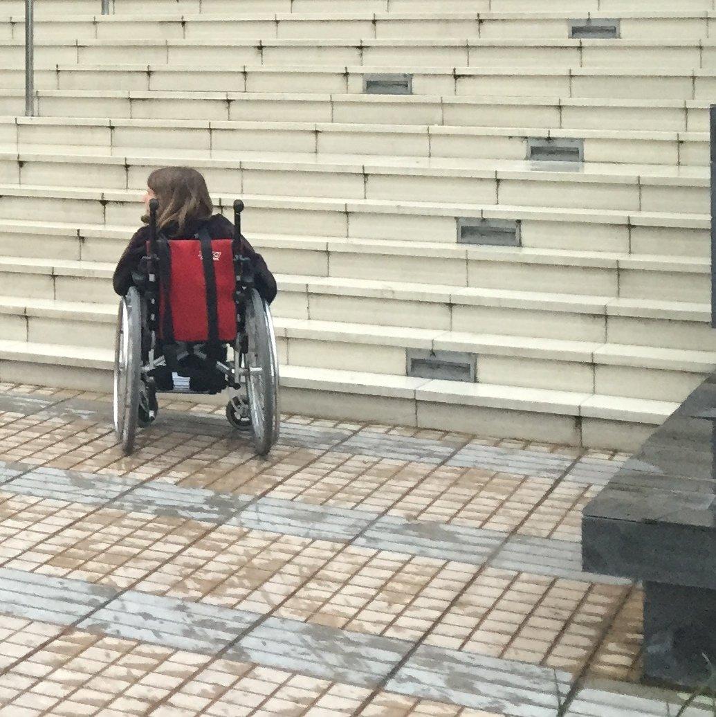 Joven en silla de ruedas enfrentando peldaños de una escalera. Un edificio sin acecsibilidad