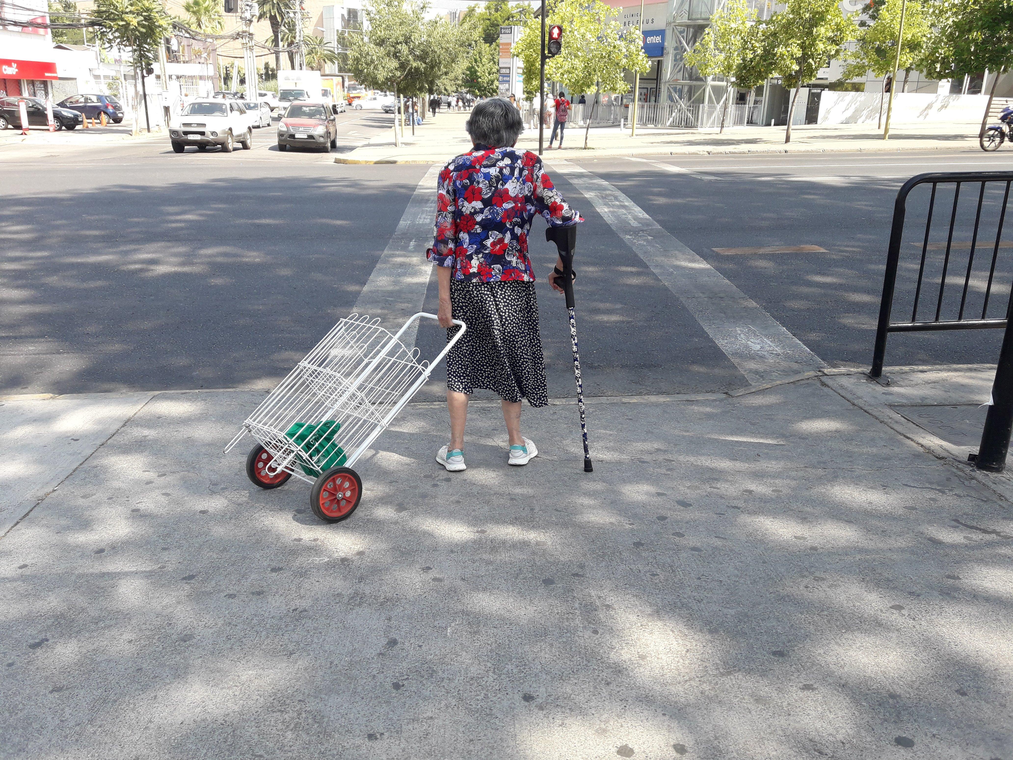 Persona mayor con bastón y un carro de compras enfrentando un cruce peatonal
