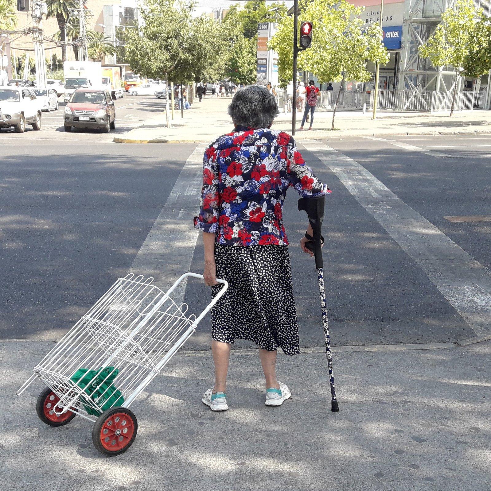 Persona mayor con bastón y un carro de compras enfrentando un cruce peatonal-001
