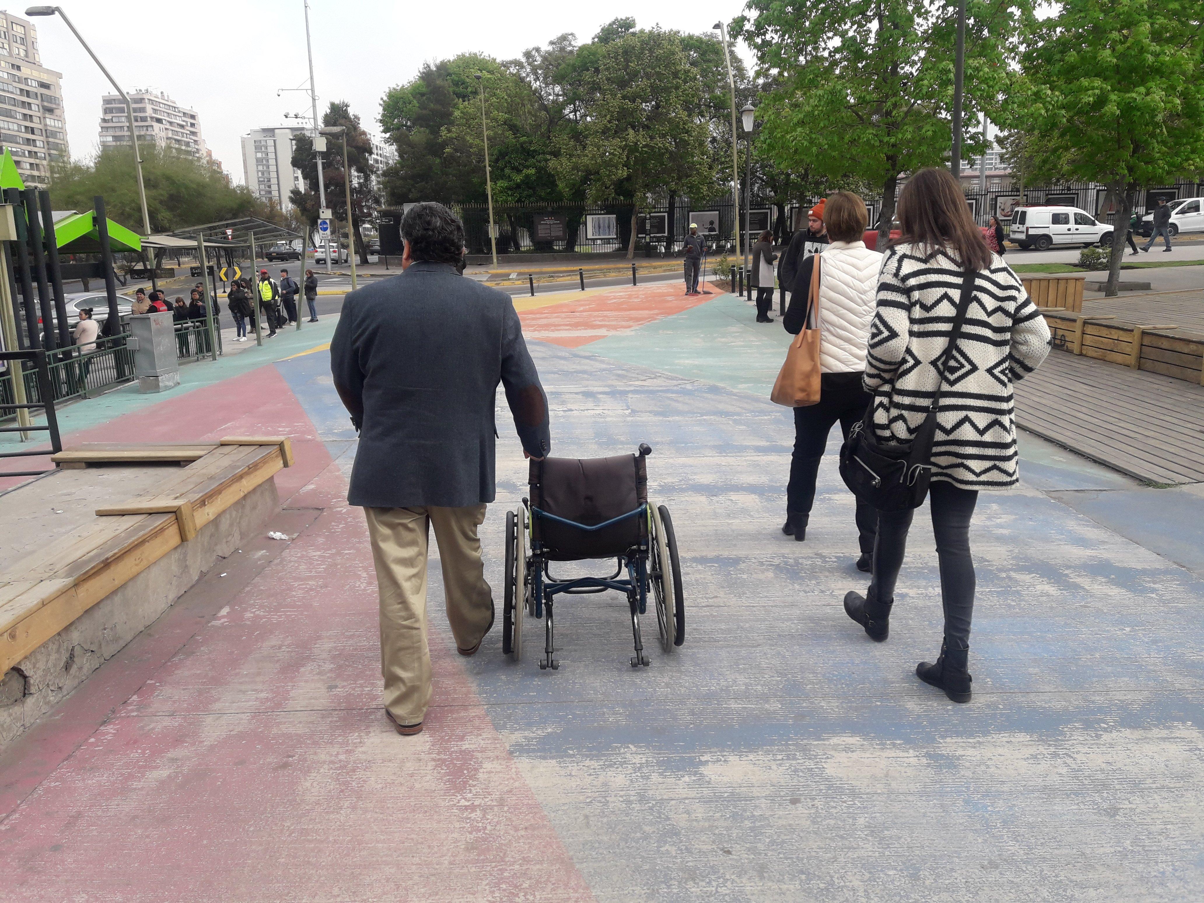 arquitecta claudia riquelme y directora de ciudad accesible en visita a terreno en calle Apoquindo junto a Miguel Latapiat de la municipalidad de las condes llevando una silla de ruedas