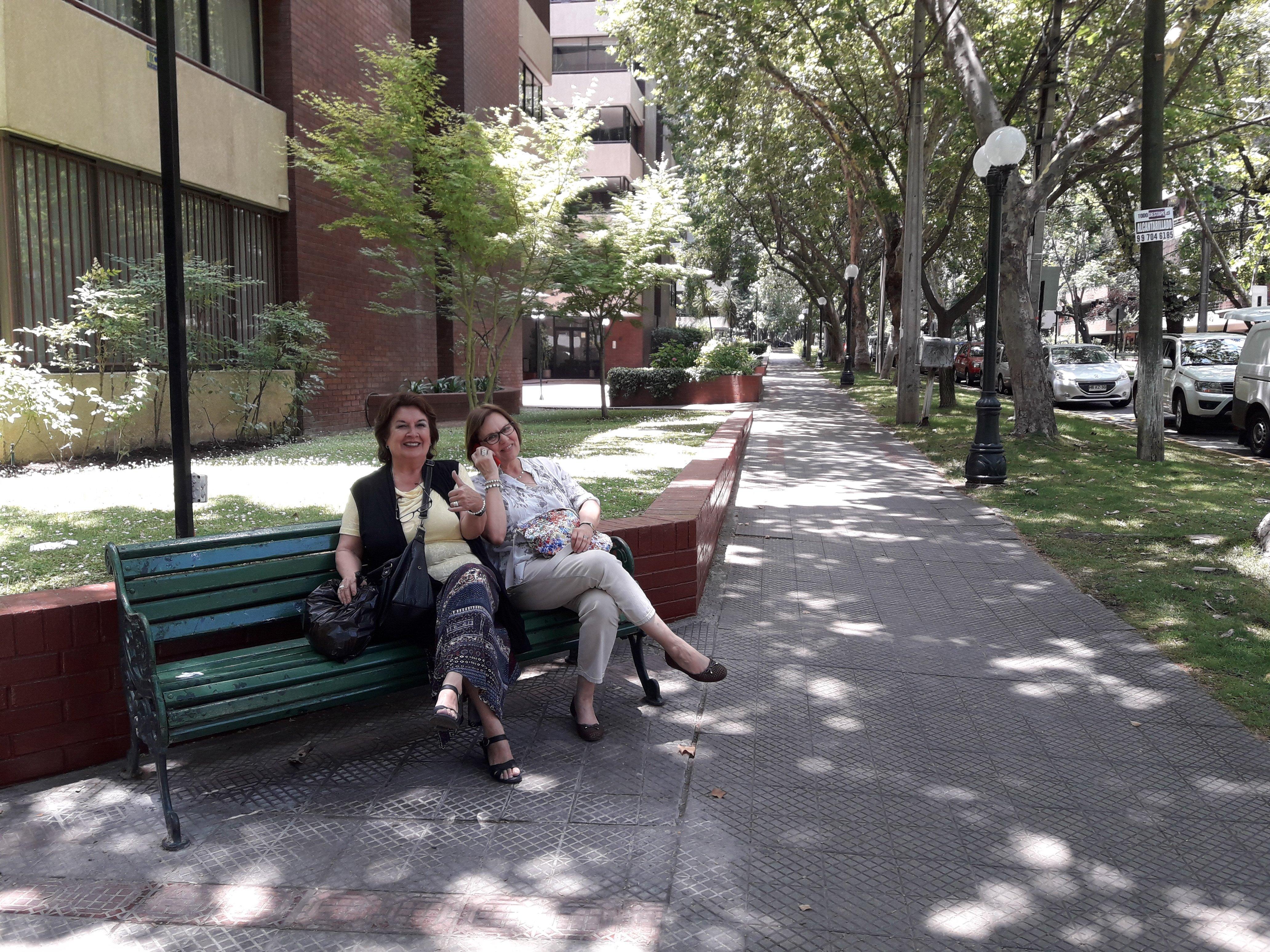 dos personas mayores descansan en un escaño ubicado en la vereda
