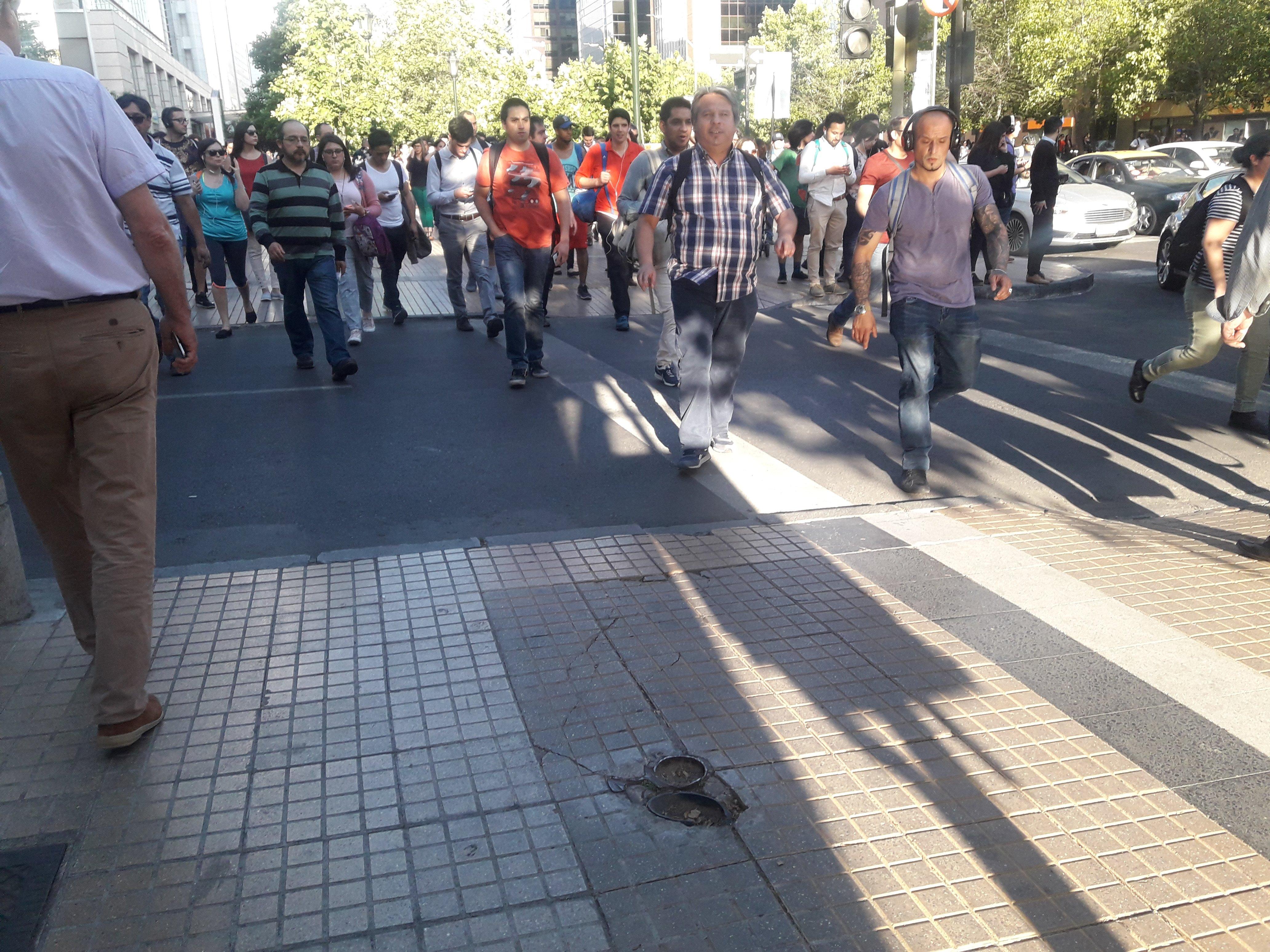 gran cantidad de peatones circulando por una vereda de las condes