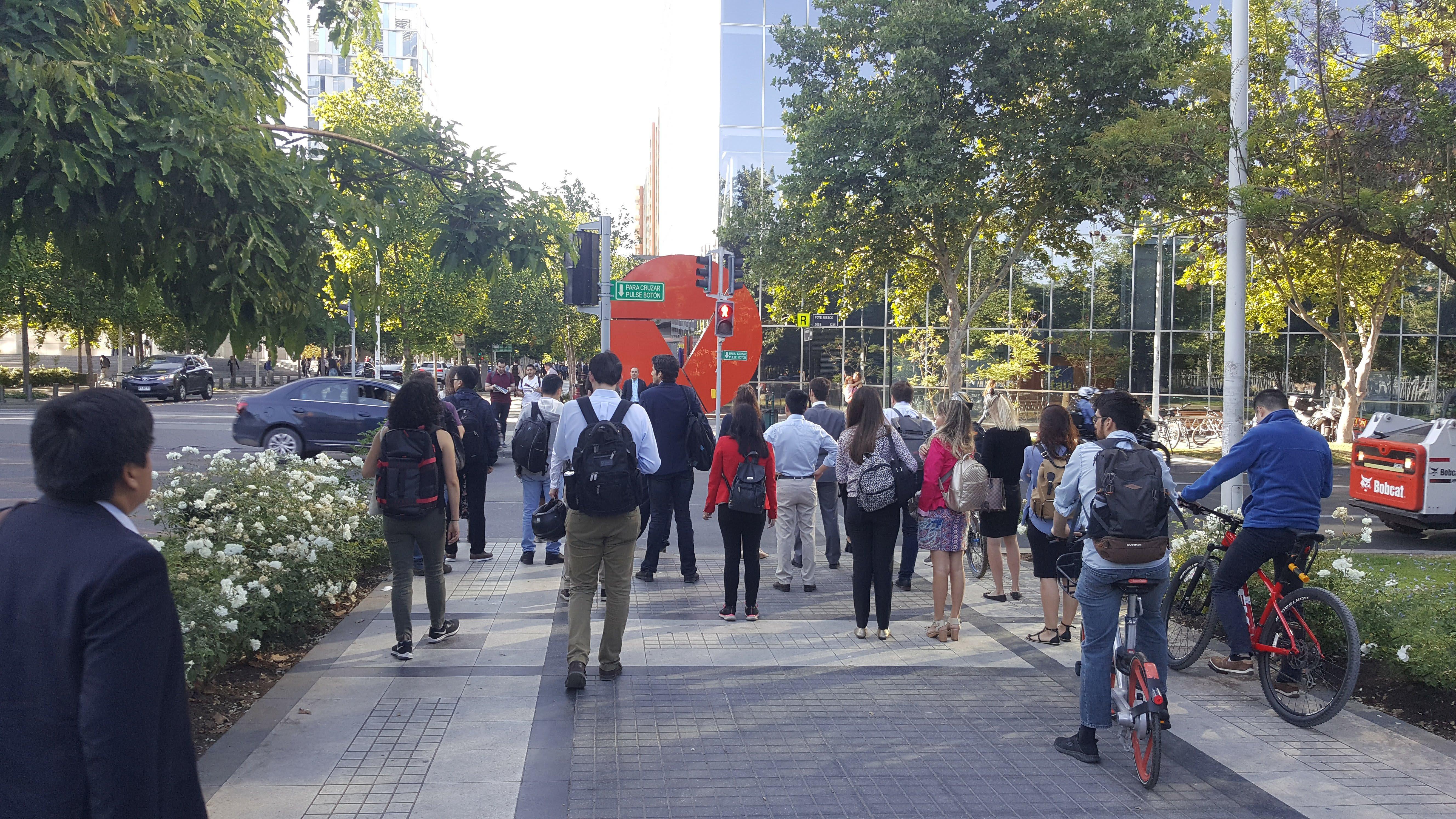 gran cantidad de peatones y varios ciclistas esperando el cruce de la calzada