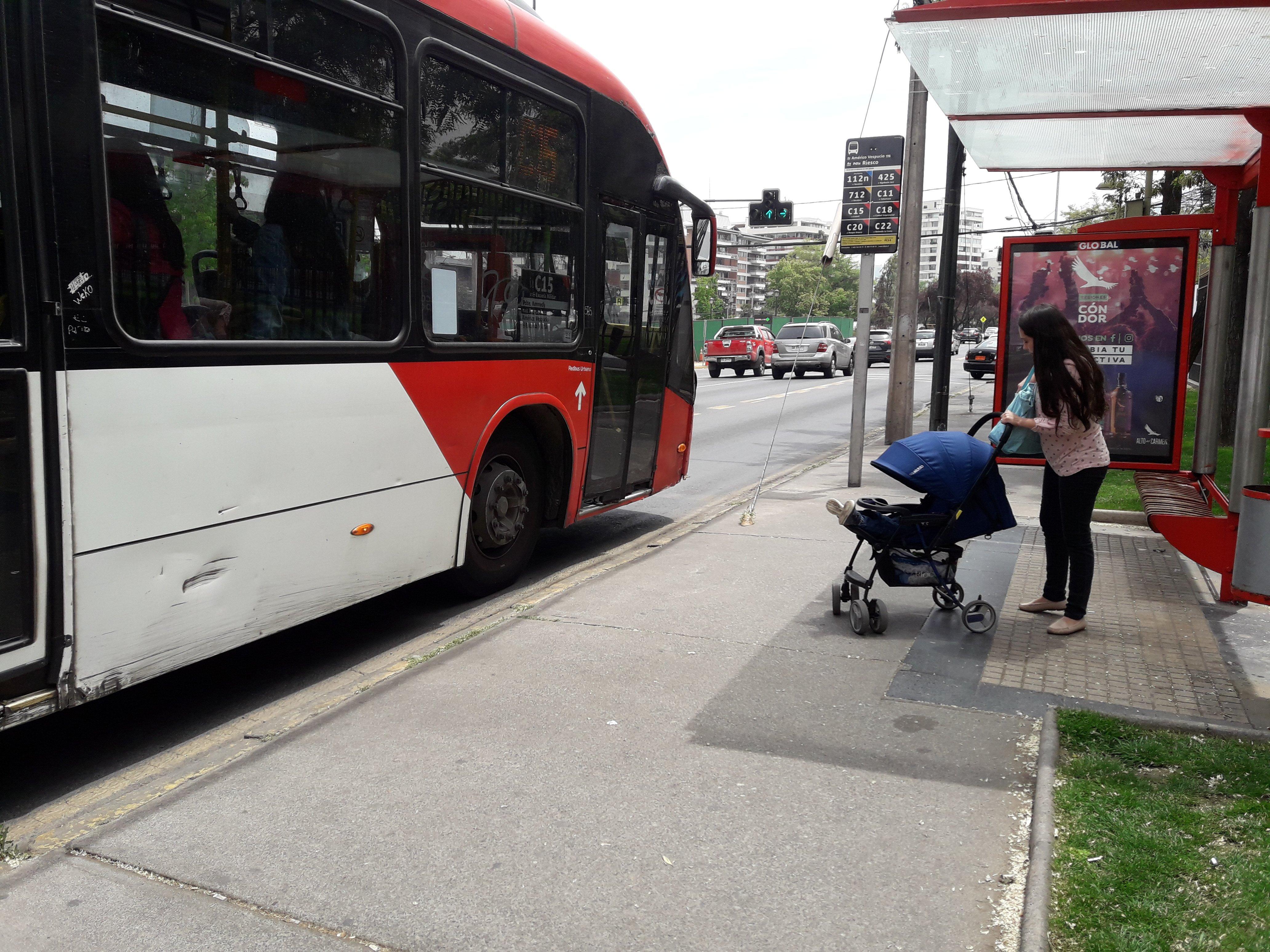 mujer con coche de niños esperando locomoción en un paradero