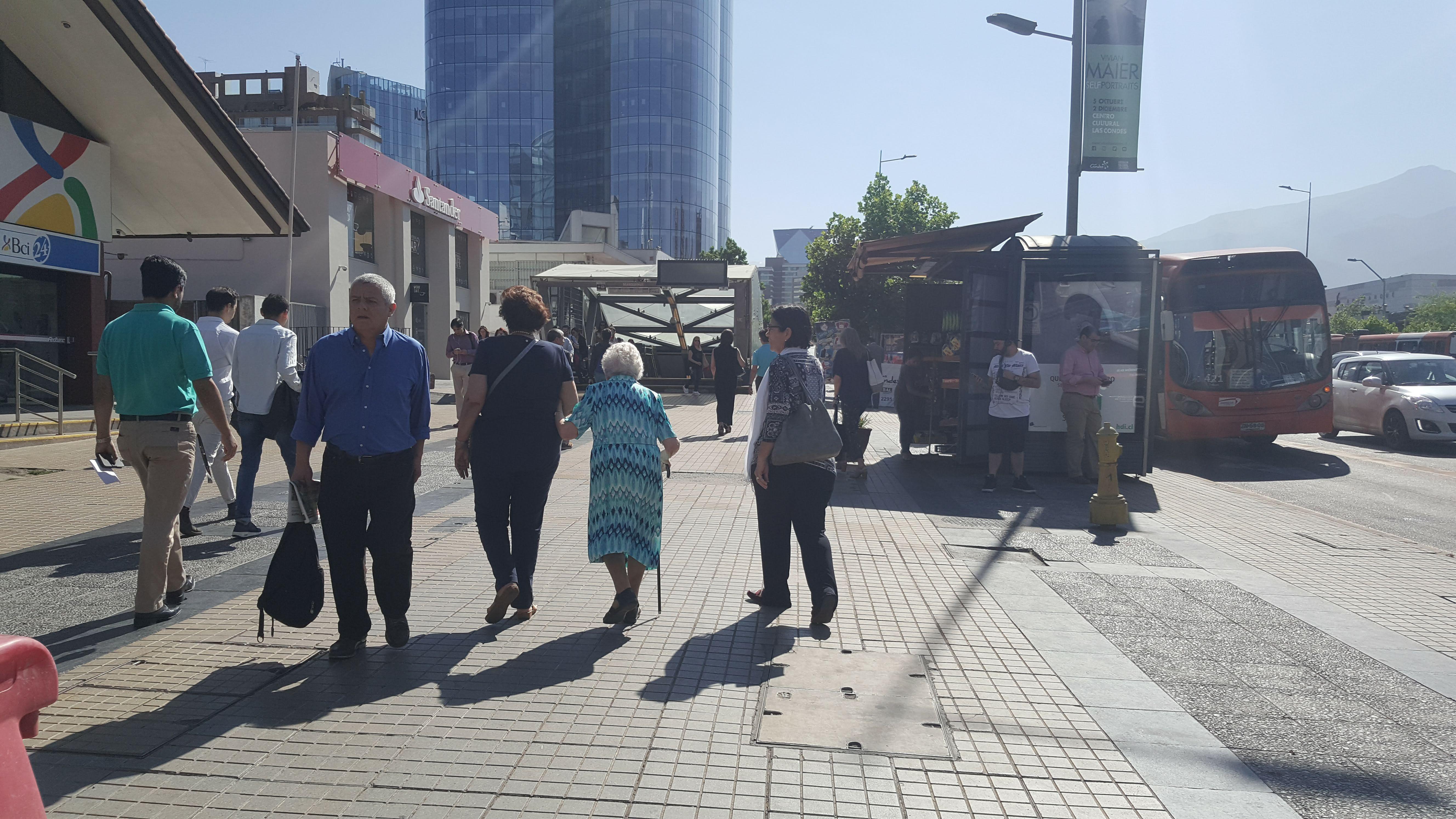 una persona adulta mayor y otros peatones por la vereda de calle apoquindo comuna de Las Condes