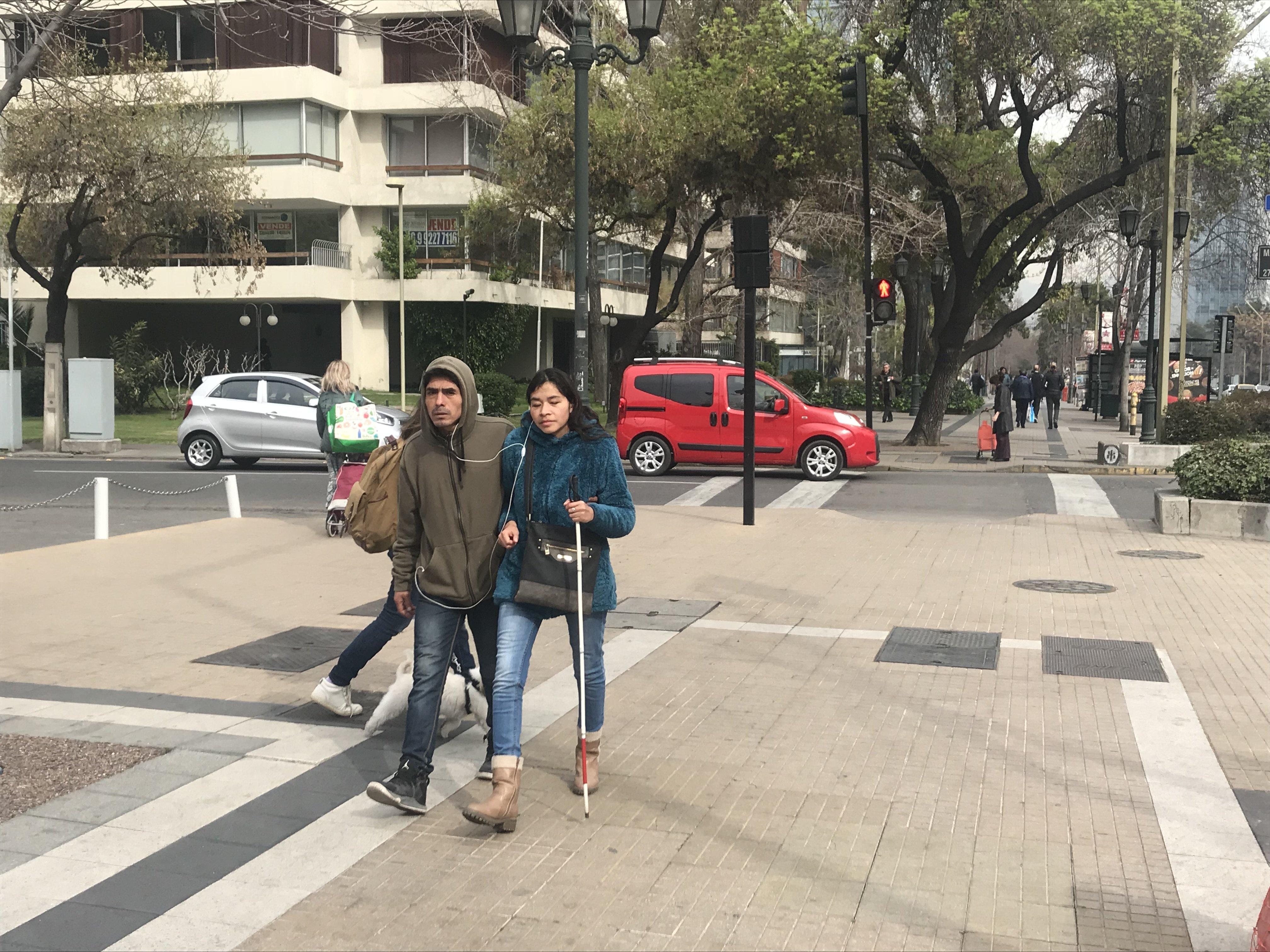 una persona ciega con acompañante circulando por una vereda de calle apoquindo comuna de Las Condes