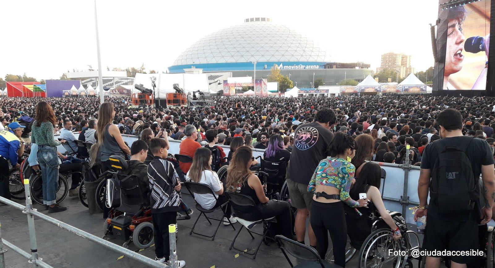 varias personas en silla de ruedas con sus acompañantes en sectores elevados para espectadores en silla de ruedas con vista al escenario