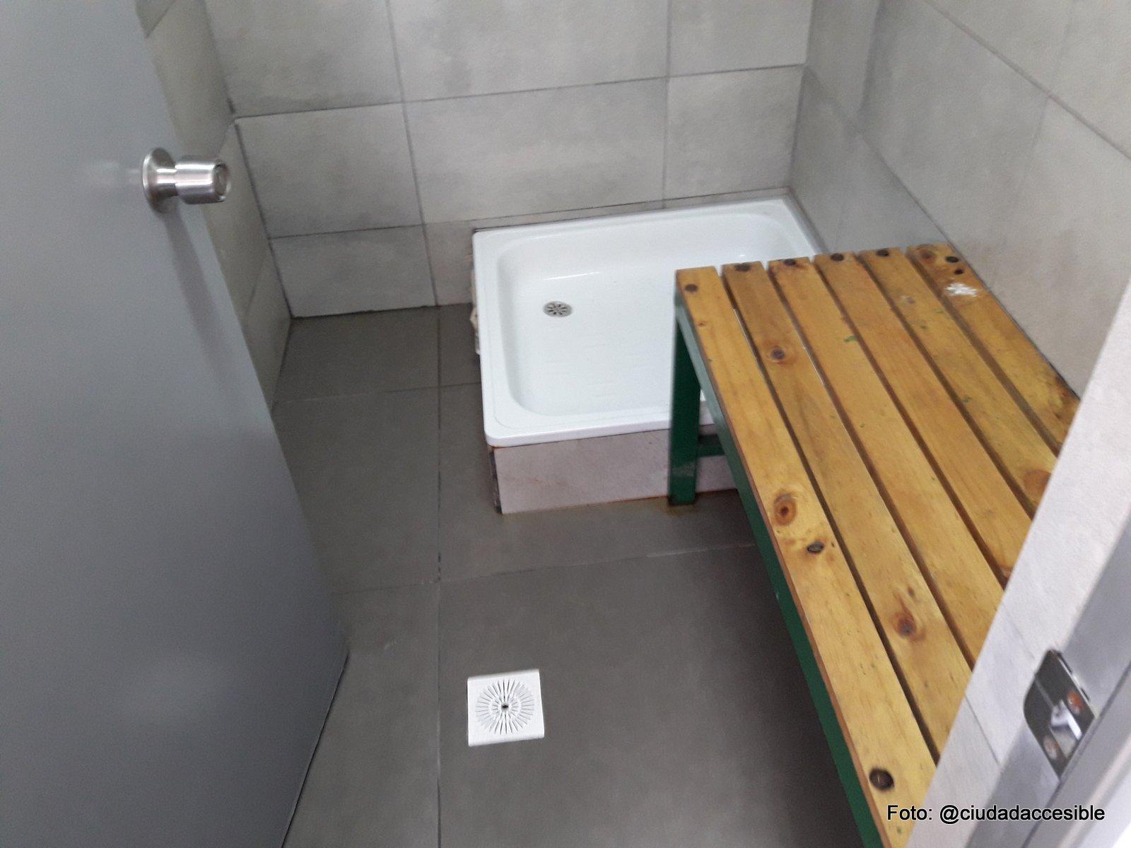 interior de ducha pública se ve un receptáculo de ducha y una banca