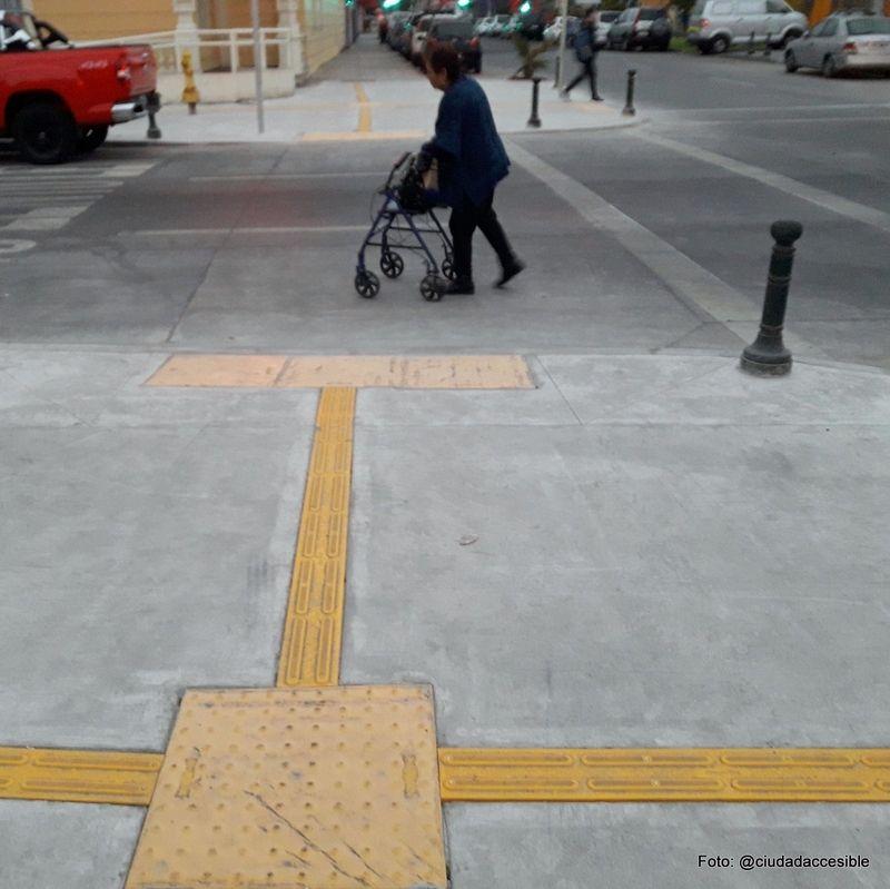 mujer con andador cruzando la calzada en una de las esquinas intervenidas en Iquique