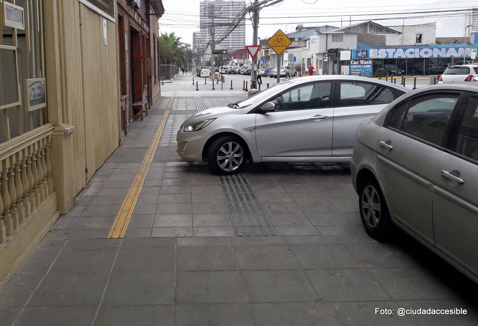autos estacionados sobre la vereda uno de ellos casi encima de la guía podotáctil de avance