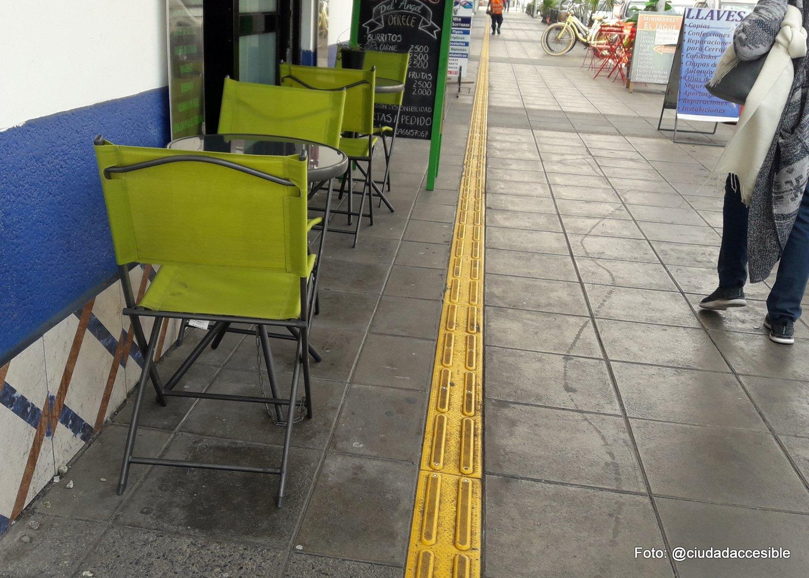 guía podotáctil de avance a lo largo de una vereda y paralela a la línea de fachada con asientos y letreros muy cercanos a ésta