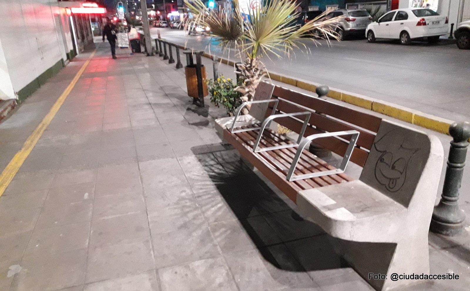 guía podotáctil de avance a lo largo de una vereda y paralela a la línea de fachada y asientos dispuestos en línea con la calzada