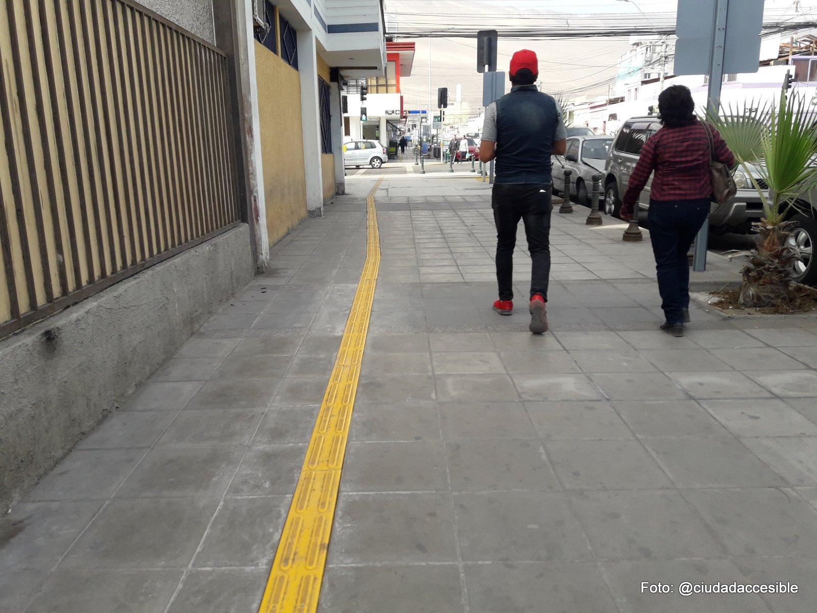 guía podotáctil de avance a lo largo de una vereda y paralela a la línea de fachada