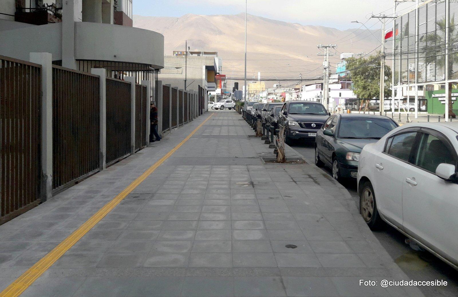 guía podotáctil de avance a lo largo de una vereda y paralela a una edificación