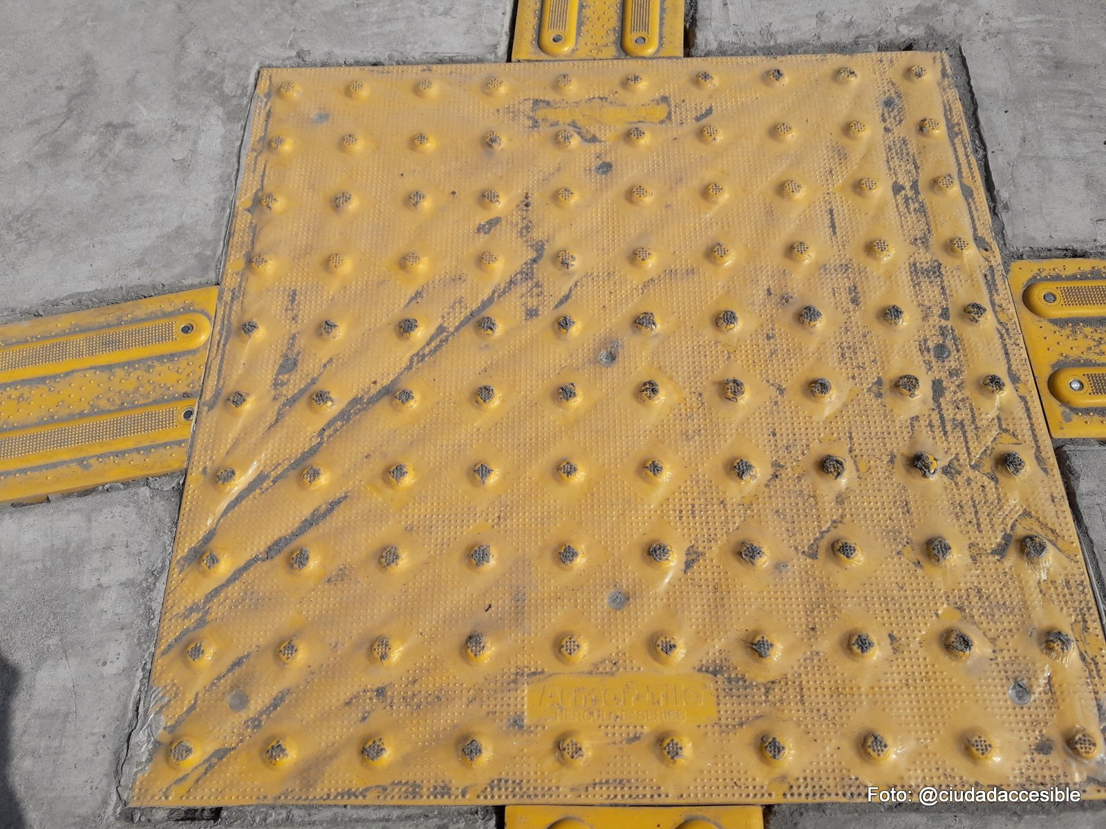 rebaje amplio de tres pendientes con placa podotáctiles de textura de alerta color amarillo embutida en el pavimento