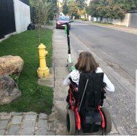 Joven en silla de ruedas por una vereda angosta enfrentando un scooter estacionado en la mitad