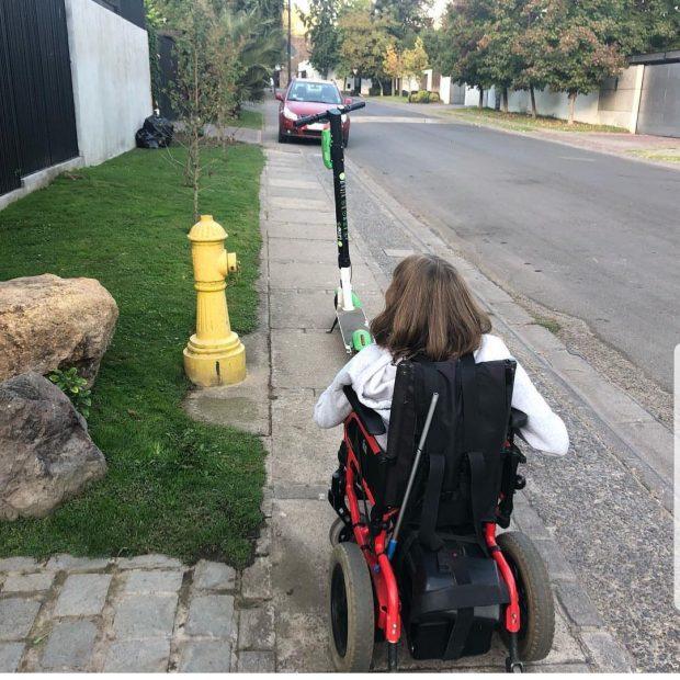 Joven con discapacidad en silla de ruedas  enfrentando un scooter estacionado en la mitad una angosta vereda