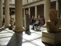 adulto mayor en silla de ruedas observando una escultura en un museo