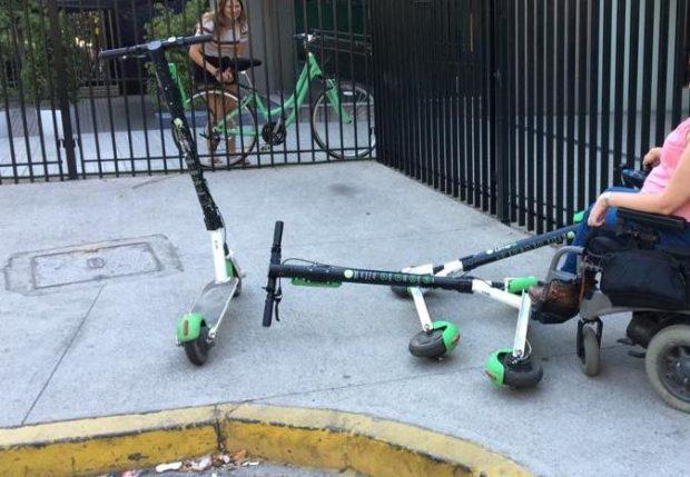 Los scooter son elementos de micro-movilidad. En la fotografía una mujer con discapacidad en silla de ruedas enfrentando tres scooter tirados sobre la vereda.