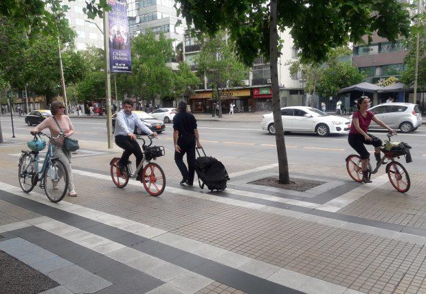La micro-movilidad en la ciudad. En la fotografía dos ciclistas circulan sobre una vereda y otra va caminando y llevando la bicicleta.