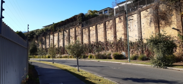 calzada y vereda con una diferencia normal y permanente de diferencia. Se ve un murallón de gran altura y varias casa edificadas en un terreno de pronunciada pendiente.