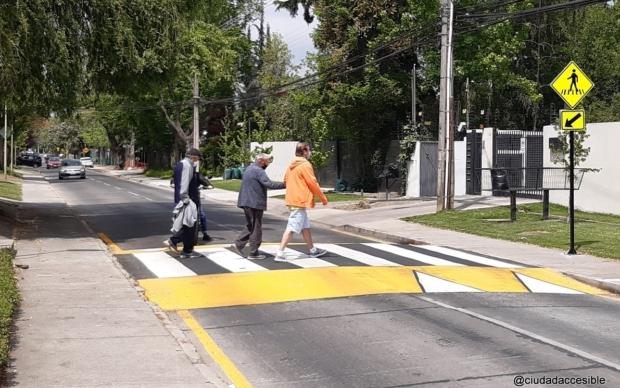tres personas, una de ellas asistida, cruzan sobre un cruce peatonal continuo a nivel vereda.