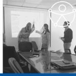 tres personas analizan una información proyectada en una pantalla